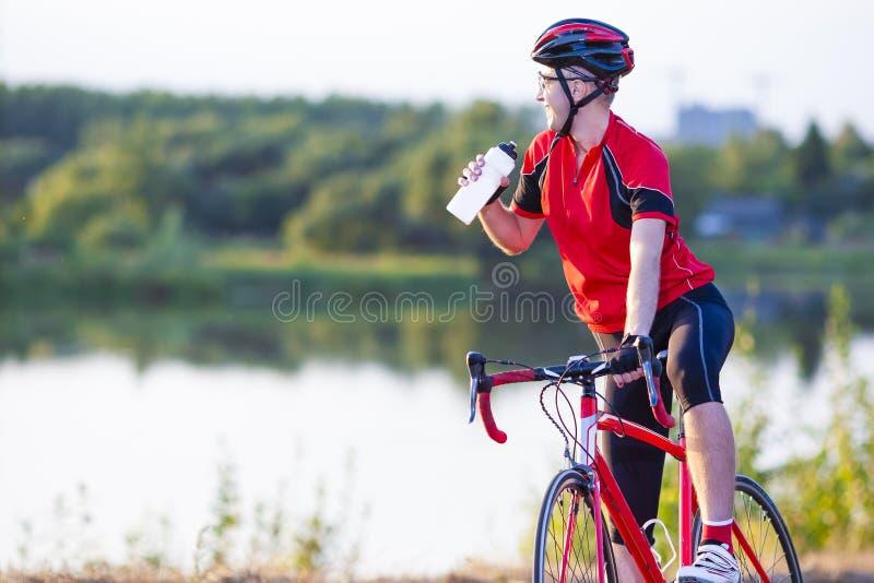 Męski cyklista Ma odpoczynek Pije Odświeżającego ciecz od butelki zdjęcia royalty free