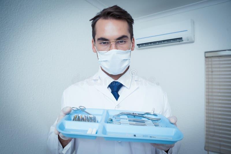 Męski dentysta w chirurgicznie maski mienia tacy narzędzia fotografia stock