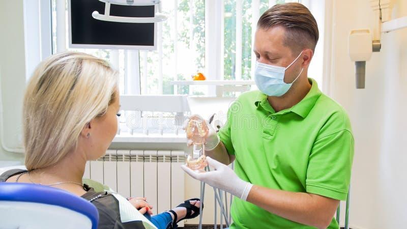 Męski dentysta wyjaśnia zębu traktowanie jego pacjent obraz royalty free