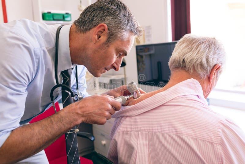 Męski dermatolog egzamininuje starszego pacjenta z dermatoscopy zdjęcie royalty free