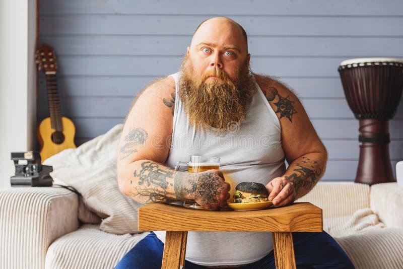 Męski fatso pije alkohol z szybkim żarciem obraz stock