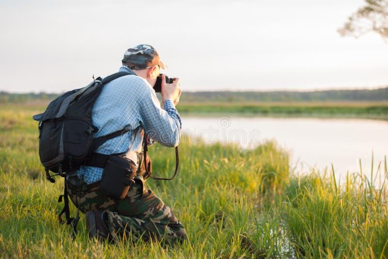 Męski fotograf patrzeje jezioro podczas zmierzchu, obrazy stock