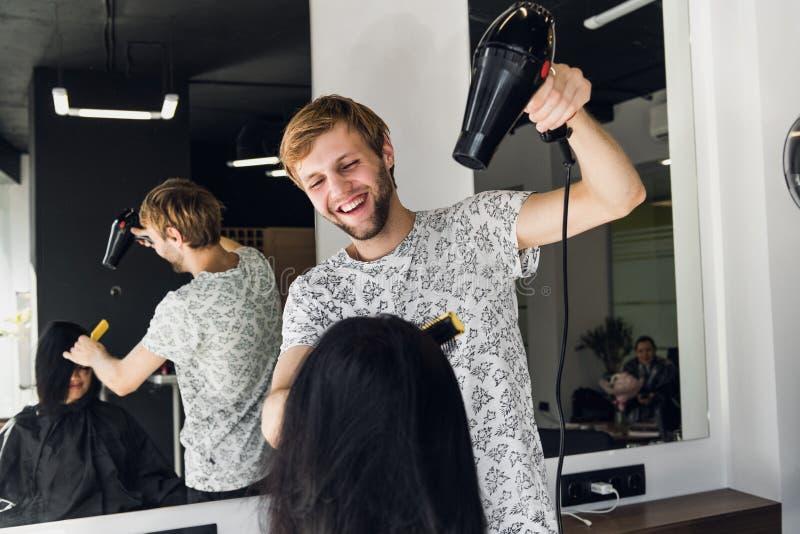 Męski fryzjer ono uśmiecha się i opowiada z klientem podczas gdy robić nowemu ostrzyżeniu piękna młoda brunetki kobieta zdjęcia stock