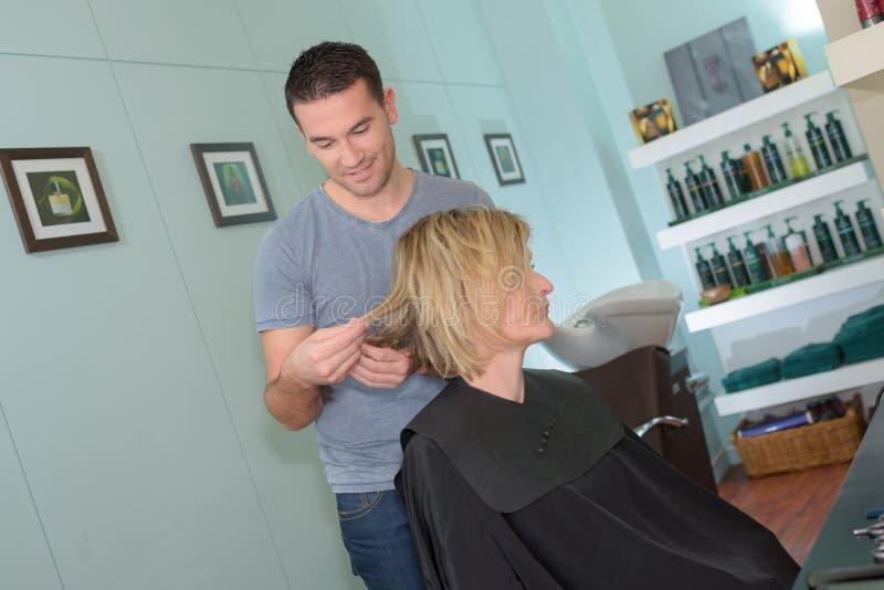 Męski fryzjer robi fryzurze dla dziewczyny przy włosianym salonem obrazy stock