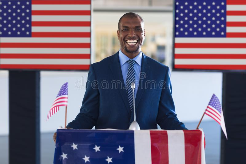 Męski głośnikowy ono uśmiecha się przy podium stołem w biznesowym konwersatorium zdjęcia royalty free