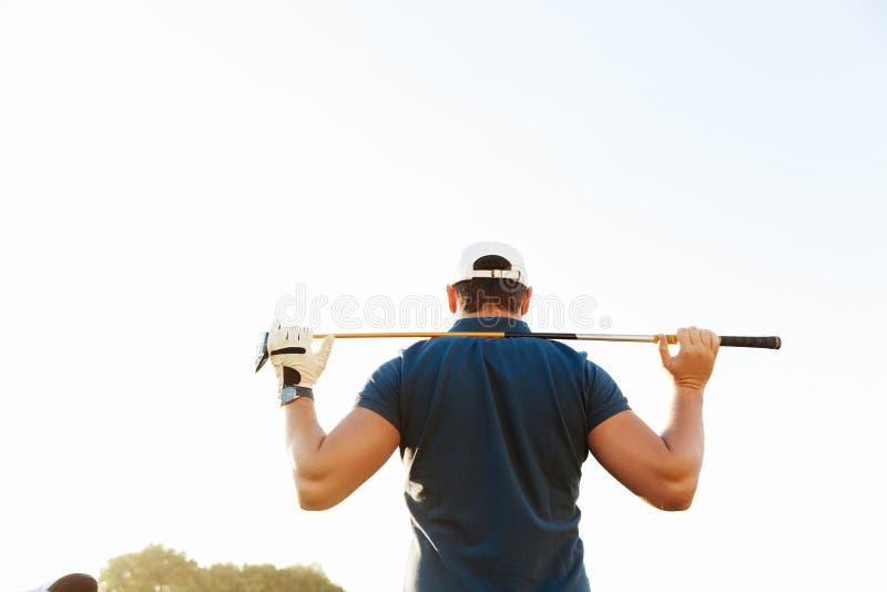 Męski golfisty mienia kierowca podczas gdy stojący na zielonym kursie obraz royalty free