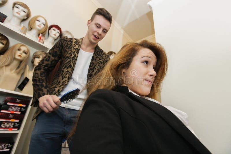 Męski hairstylist szczotkuje żeńskiego klienta włosy w salonie zdjęcia stock