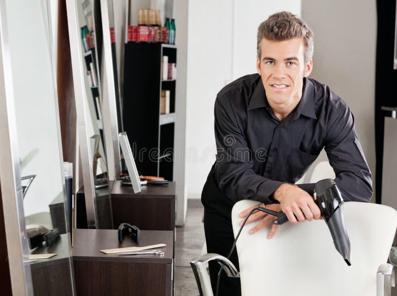 Męski Hairstylist Z Hairdryer Opiera Na krześle obraz stock