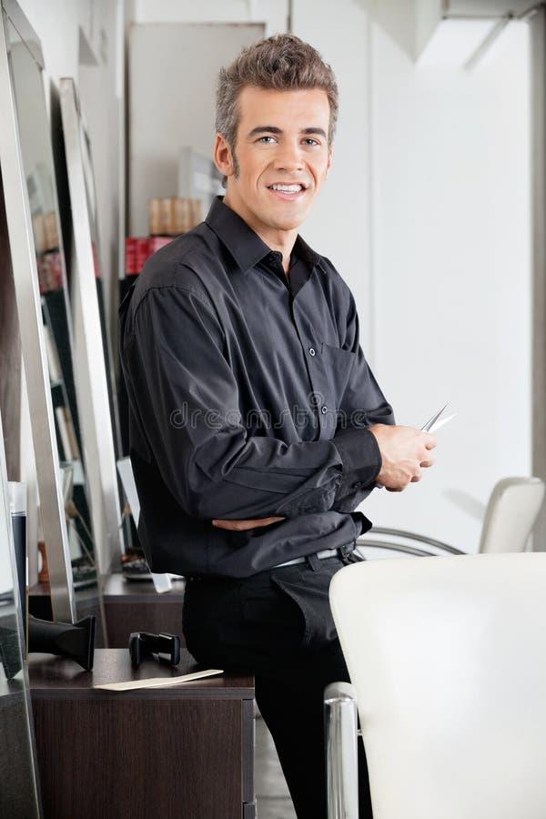 Męski Hairstylist Z nożycami Opiera Na gabinecie zdjęcie royalty free