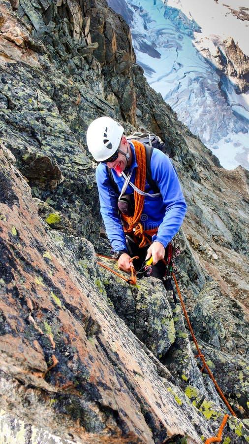 Męski halny przewdonik buduje tradycyjną belay postawę z pitons rappel od wysokiego wysokogórskiego szczytu zdjęcia stock