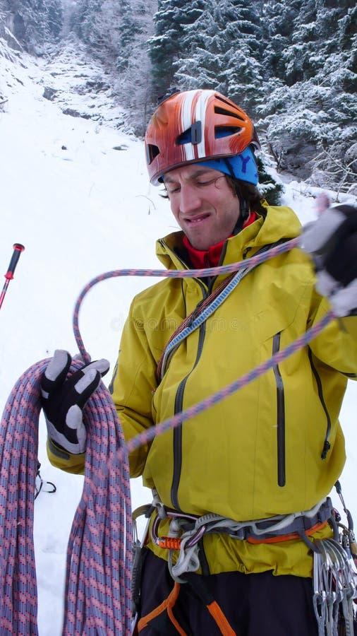 Męski halny przewdonika narządzanie wspinać się stromą marznącą siklawę na zimnym zima dniu w Alps obrazy stock