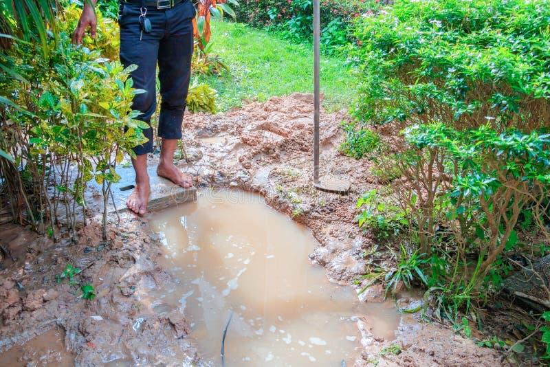 Męski hydraulik jest naprawa łamającym drymbą w dziurze z instalaci wodnokanalizacyjnej wody przepływem plenerowym i światło słon obraz royalty free