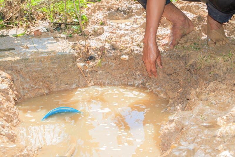 Męski hydraulik jest naprawa łamającym drymbą w dziurze z instalaci wodnokanalizacyjnej wody przepływem plenerowym i światło słon obraz stock