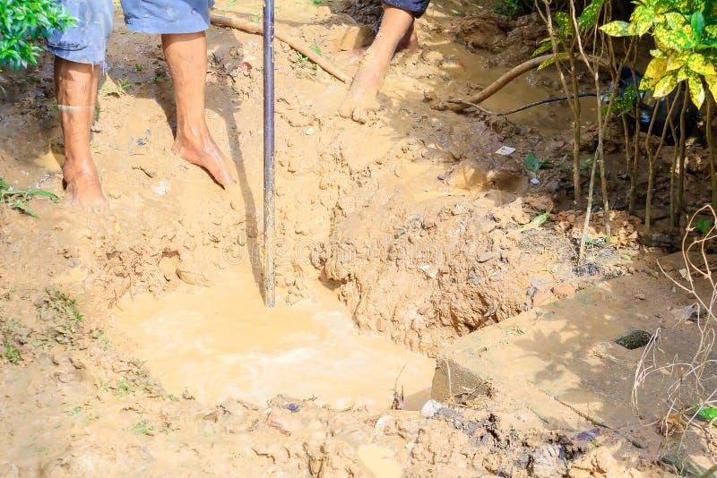 Męski hydraulik jest naprawa łamającym drymbą w dziurze z instalaci wodnokanalizacyjnej wody przepływem plenerowym i światło słon zdjęcia stock