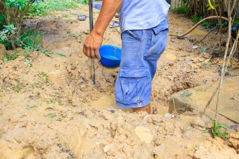 Męski hydraulik jest naprawa łamającym drymbą w dziurze z instalaci wodnokanalizacyjnej wody przepływem plenerowym i światło słon zdjęcie royalty free