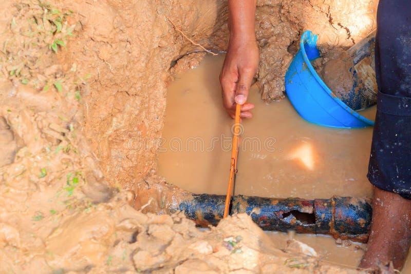 Męski hydraulik jest naprawa łamającym drymbą w dziurze z instalaci wodnokanalizacyjnej wody przepływem plenerowym i światło słon obrazy stock