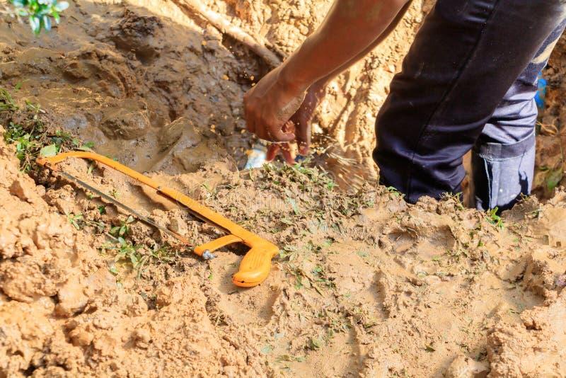 Męski hydraulik jest naprawa łamającym drymbą w dziurze z instalaci wodnokanalizacyjnej wody przepływem plenerowym i światłem sło fotografia royalty free