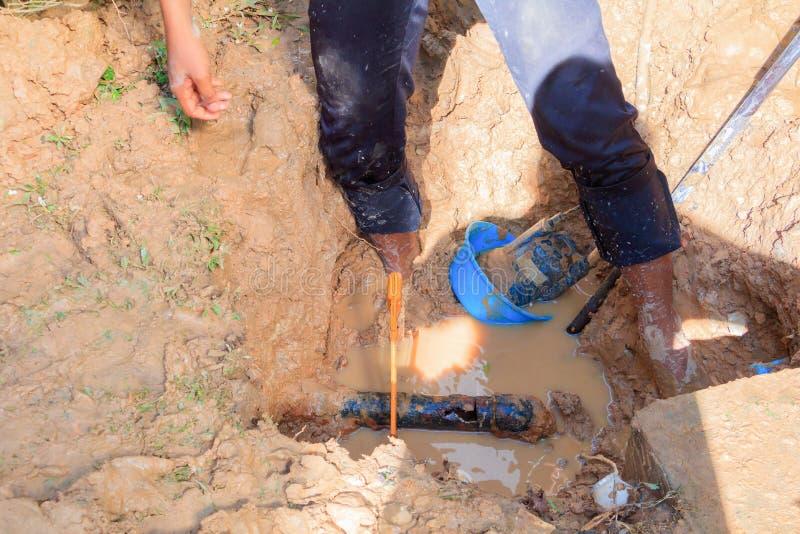 Męski hydraulik jest naprawa łamającym drymbą w dziurze z instalaci wodnokanalizacyjnej wody przepływem plenerowym i światłem sło zdjęcia royalty free