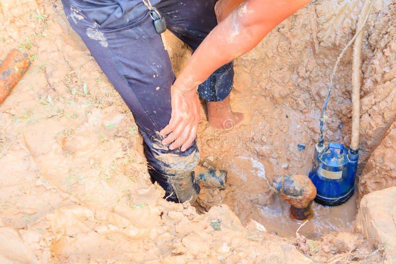 Męski hydraulik jest naprawa łamającym drymbą w dziurze z instalaci wodnokanalizacyjnej wody przepływem plenerowym i światłem sło obraz stock