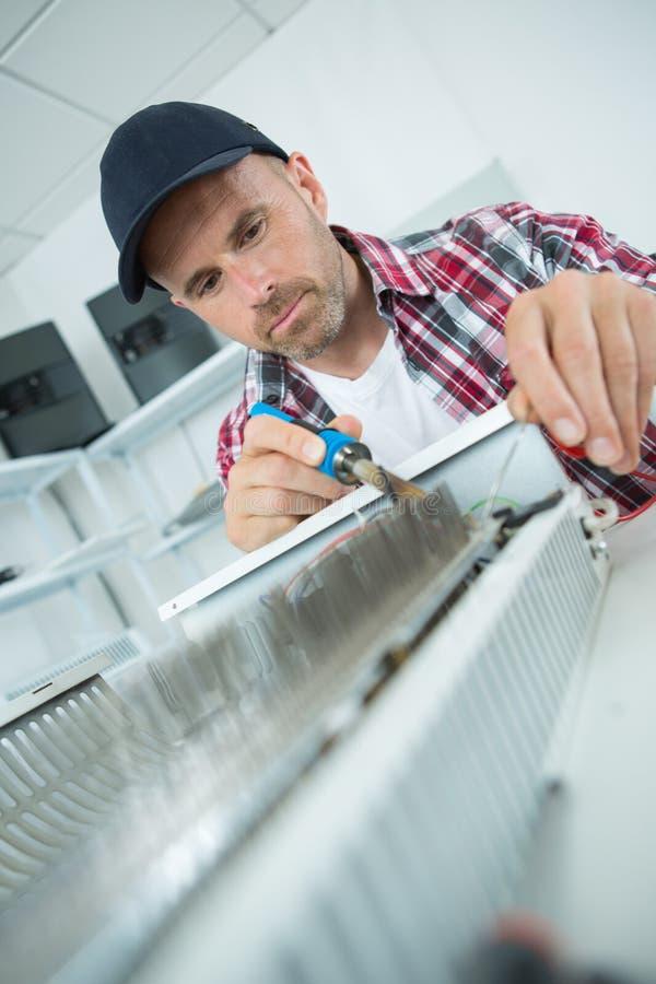 Męski hydraulika naprawiania grzejnik z lutowniczym żelazem zdjęcie royalty free