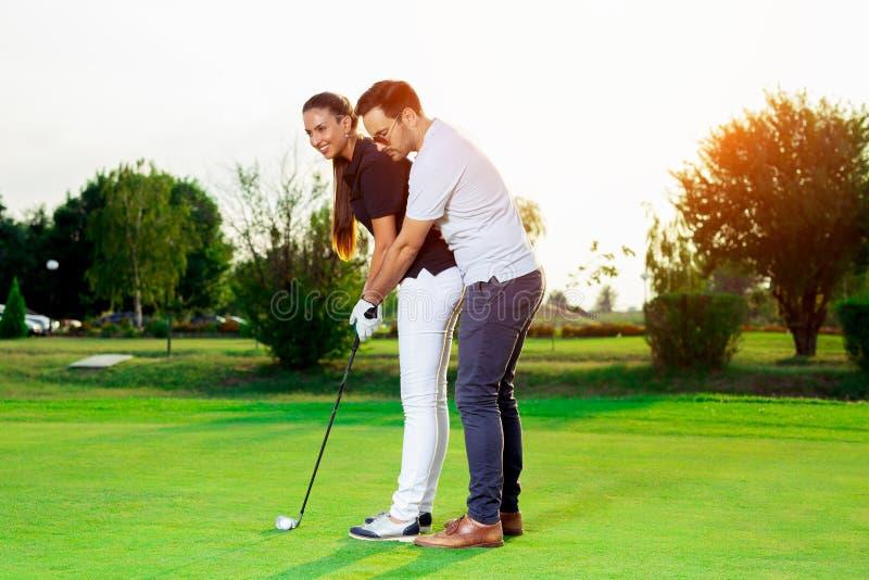 Męski instruktor pokazuje kobiety bawić się golfa zdjęcia stock