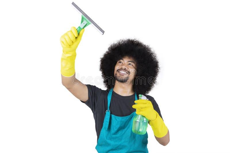 M?ski janitor czy?ci lustro w studiu obrazy stock