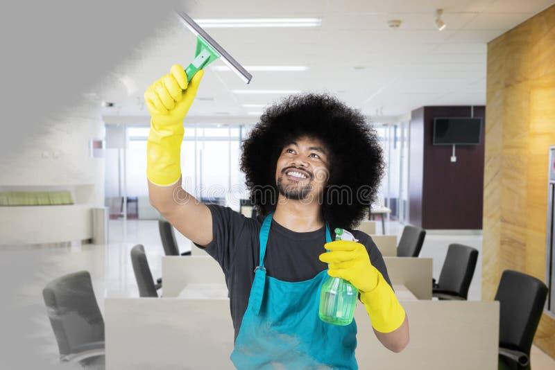 Męski janitor czyści zakurzonego lustro w biurze zdjęcia royalty free