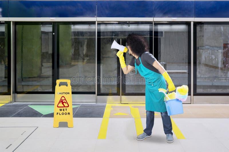 Męski janitor używa megafon w dworcu zdjęcia stock