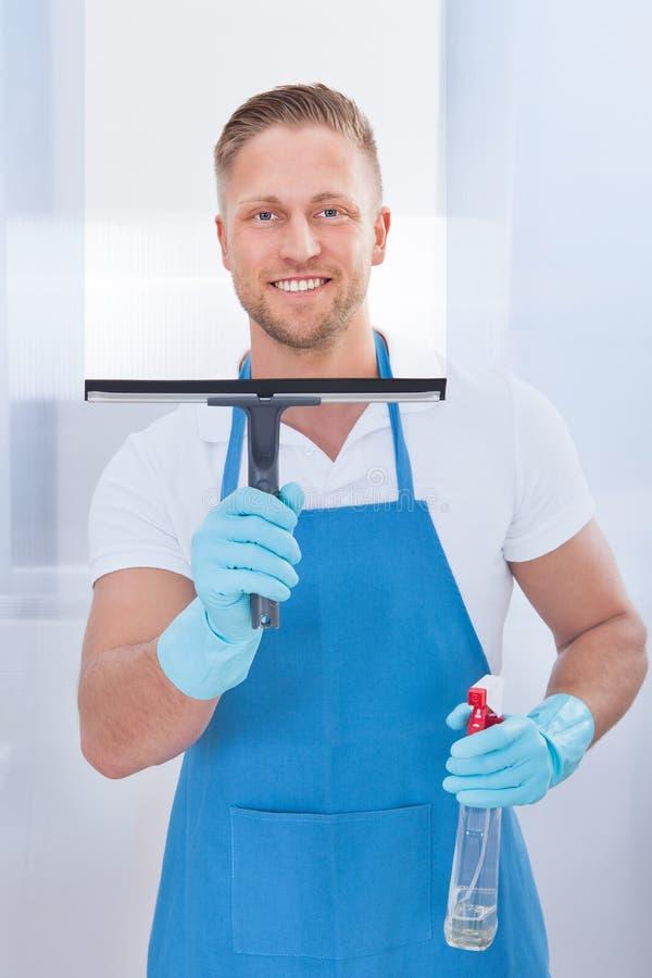 Męski janitor używa squeegee czyścić okno fotografia royalty free