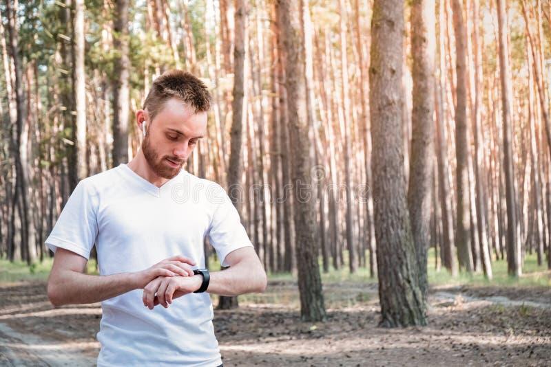 Męski jogeer sprawdza mądrze zegarek outdoors zdjęcia royalty free