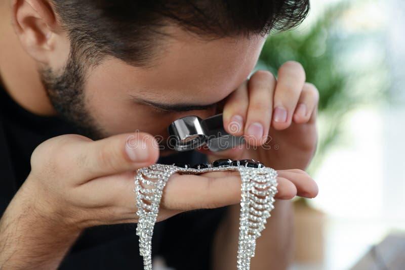 Męski jubiler ocenia piękną kolię w warsztacie fotografia stock
