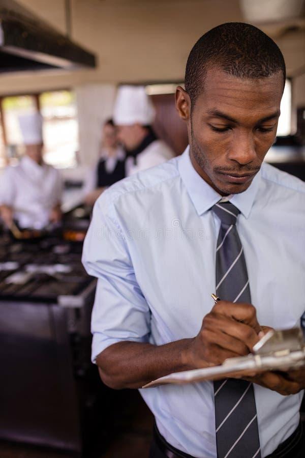Męski kierownik pisze na clipbaord w kuchni obraz stock