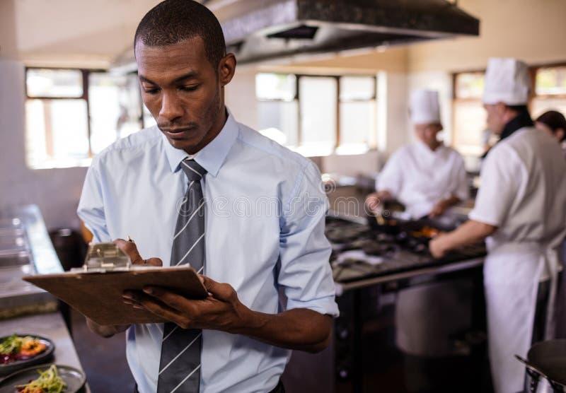 Męski kierownik pisze na clipbaord w kuchni zdjęcia stock