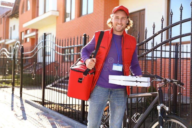 Męski kurier dostarcza jedzenie w mieście na pogodnym zdjęcia stock