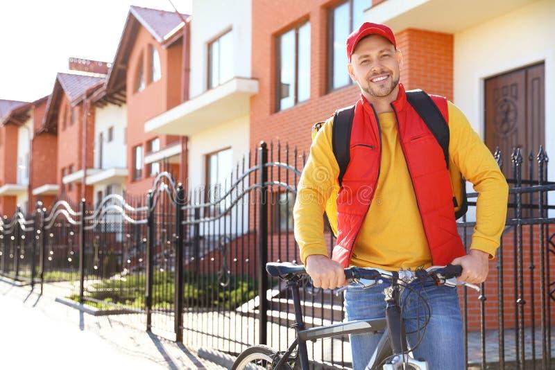 Męski kurier dostarcza jedzenie wewnątrz na bicyklu obraz stock