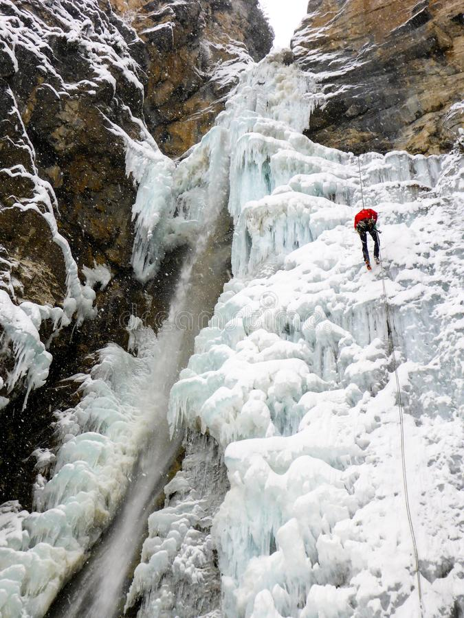 Męski lodowy arywista rappelling z niebezpiecznego nd załamuje się lodowego spadek w głębokiej zimie w czerwonej kurtce fotografia royalty free