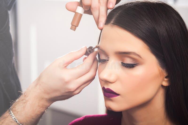 Męski makijażu artysta Barwi brwi brunetki dziewczyna w beaty salonie, zakończenie up zdjęcia royalty free
