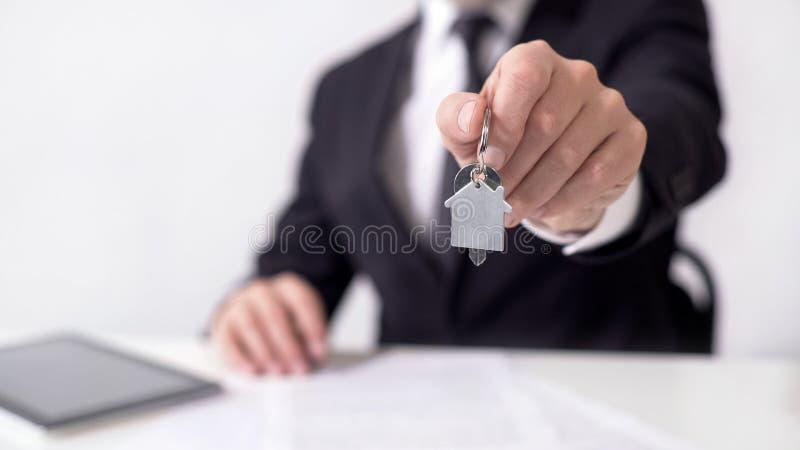Męski makler trzyma out kluczowego łańcuchu dom, podpisujący kontrakt, kupuje własność fotografia stock