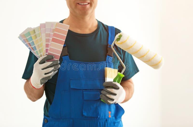 Męski malarz w mundurze z kolor palety próbkami, muśnięciem i rolownikiem indoors, fotografia stock