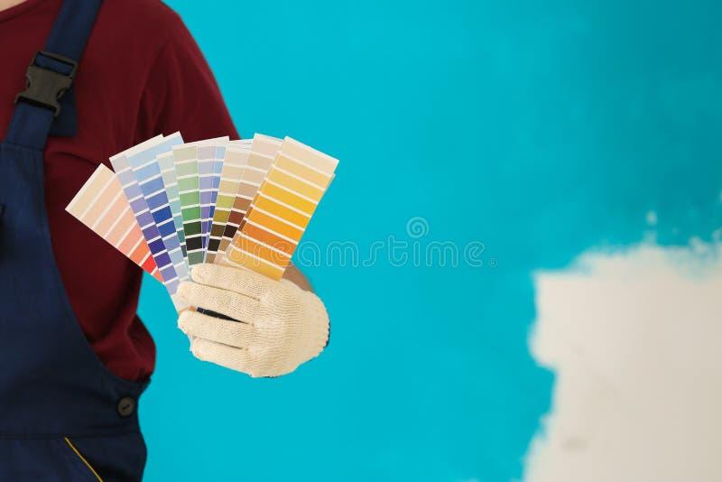 Męski malarz w mundurze z kolor palety próbkami na kolorowym tle obraz royalty free