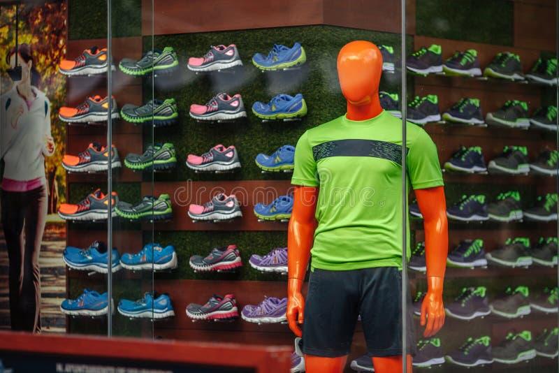 Męski mannequin w zielonej koszulce w sklepowym okno sportowych towarów sklep na tle sneakers obraz stock