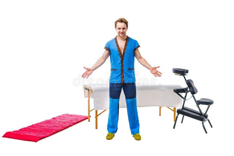 Męski masażysta w błękita munduru stojakach z gestem powitanie ręki strony z uśmiechem obok wyposażenia dla masażu stołu, fol zdjęcia royalty free