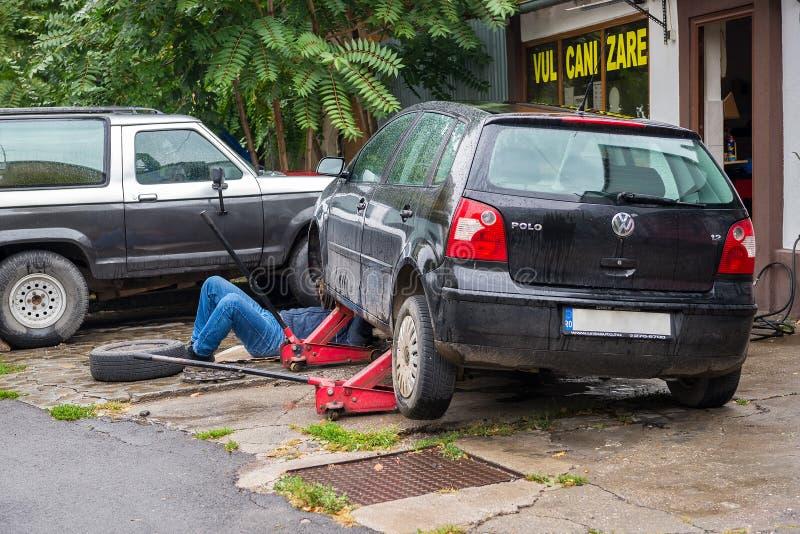 Męski mechanik pracuje pod samochodem przy małą samochód usługa obrazy stock
