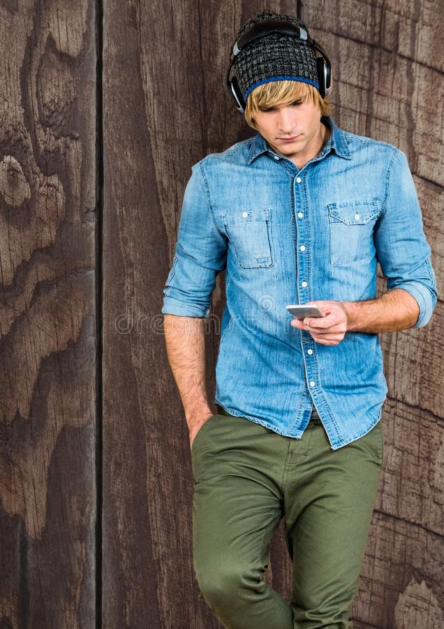 Męski modniś używa mądrze telefon przeciw drewnianej ścianie fotografia stock