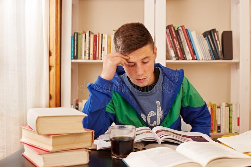 Męski nastolatek pije kolę podczas gdy studiujący zdjęcia stock