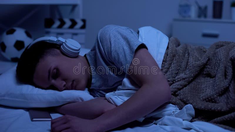 Męski nastoletni chłopak spadać uśpiony w hełmofonach, zapracowany studencki relaksować obrazy royalty free