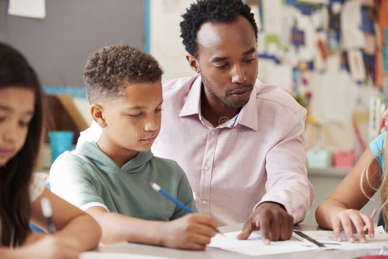 Męski nauczyciel pracuje z uczniem przy biurkiem, zamyka up obrazy royalty free