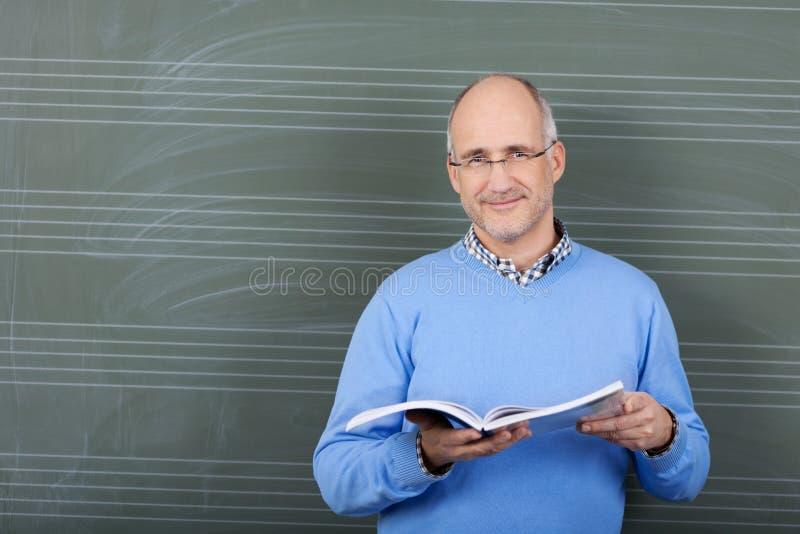 Męski nauczyciel z tekst książką w jego ręki obraz royalty free