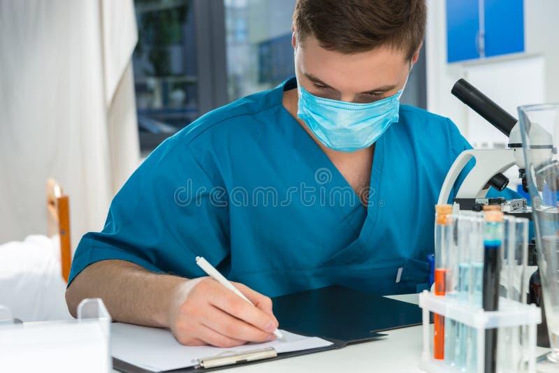 Męski naukowiec w mundurze pisze puszek notatkach jego badanie fotografia stock