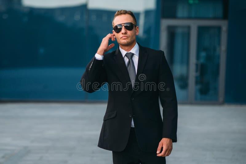 Męski ochroniarz używa ochrony earpiece outdoors zdjęcia royalty free
